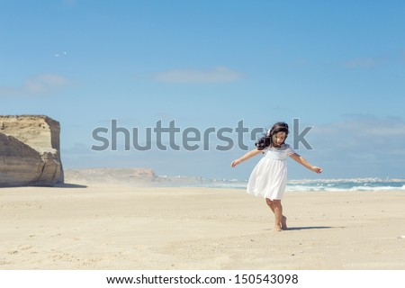 Little girl dancing on the beach with a white dress - stock photo