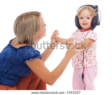Little girl dancing with headphones holding her mothers hands - isolated