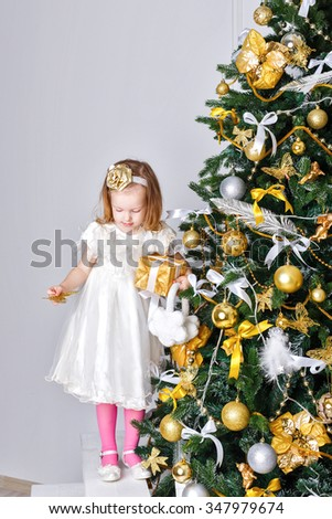Little girl decorate the Christmas tree. Party. The concept of celebration and fun. Family happiness. Childhood. - stock photo