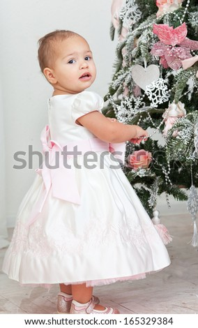 little girl decorates a Christmas Christmas tree - stock photo