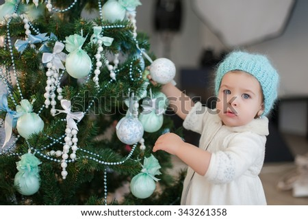Little girl decorating a Christmas tree toys, holiday, gift, decor, new year, christmas, lifestyle - stock photo