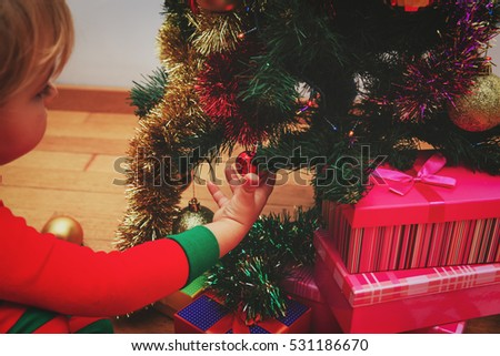 little girl decorating christmas tree in living room