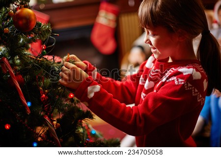 Little girl decorating Christmas tree with toys - stock photo