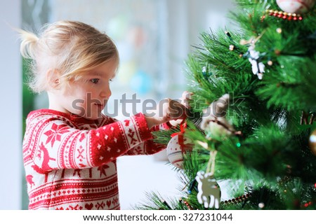 Little girl decorating christmas tree with toys and baubles. Cute kid preparing home for xmas celebration. - stock photo