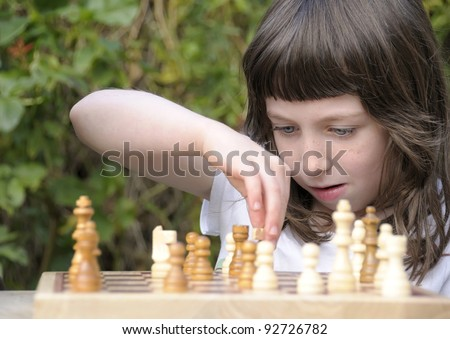 Little girl deep in thought as she contemplates her next move in a game of chess. - stock photo