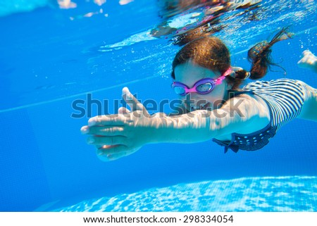 little girl deftly swim underwater in pool - stock photo