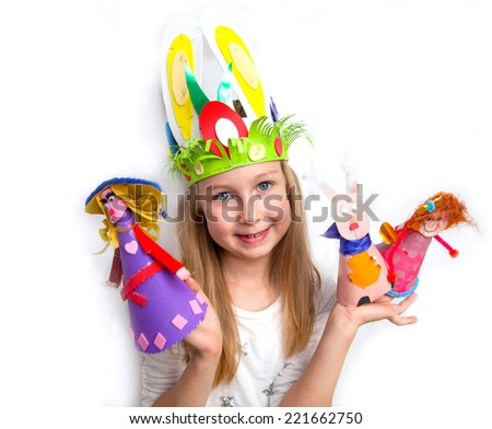 Little girl demonstrating her craft works Easter bonnet, paper dolls and reindeer - stock photo