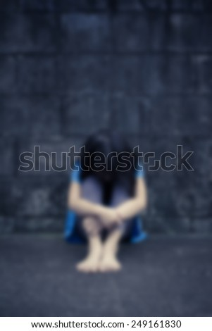 little girl despair sitting against a brick wall, Motion blurr - stock photo