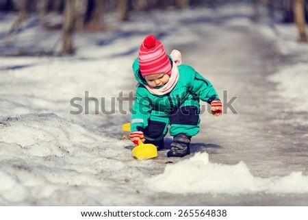 little girl digging snow in winter, kids activities - stock photo