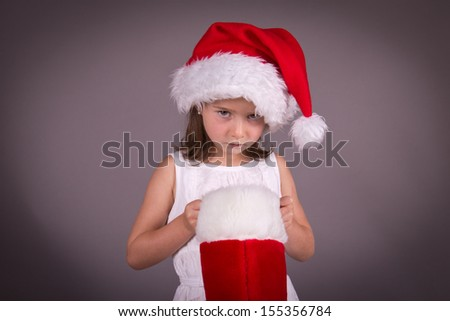 Little girl disappointed with her Christmas stocking - stock photo