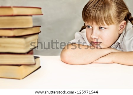 Little girl discontentedly looking at piles of books - stock photo