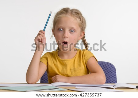 Little girl discovers the world and that is why she is very amazed by the new information she got. Opened mouth and big blue eyes show real amazement. Young girl holds a pencil in her hand.