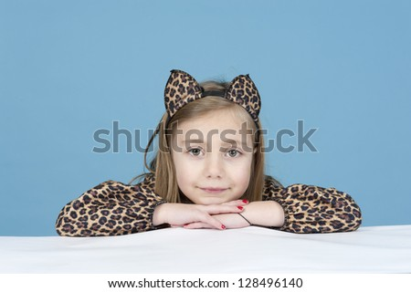 little girl disguised as a leopard, isolated on blue background - stock photo