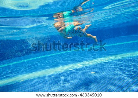 Little girl diving underwater in the pool and smiling