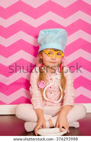little girl doctor with the hat and yellow glasses on a pink background