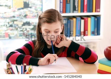 Little girl doing her school homework at a desk - stock photo