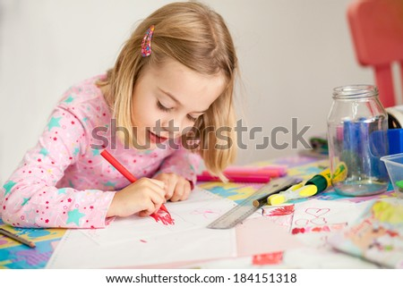 Little girl doing school work at home - stock photo