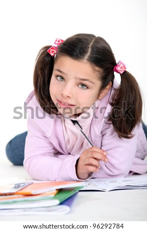 Little girl doing schoolwork - stock photo