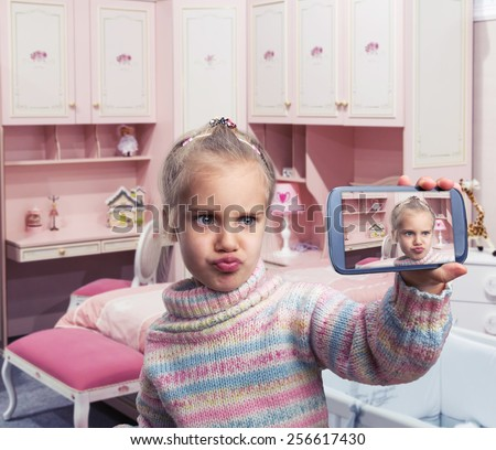 Little girl doing selfie - stock photo