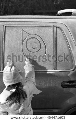 Little girl draw a happy face on a frosted car window on winter ski trip holiday vacation. Travel concept. copy space