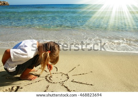 little girl draw the sun on the sand on the beach
