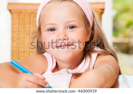 Little girl drawing and painting pictures at home or in kindergarten, she is in preschooler age