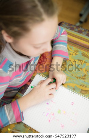 Little girl drawing and writing with coloring pencils in the block at home.
