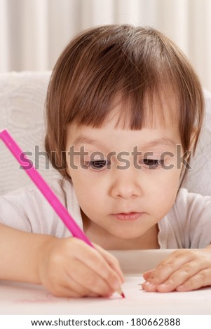 Little girl drawing at home at table