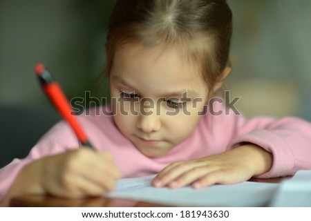Little girl drawing at home at table - stock photo
