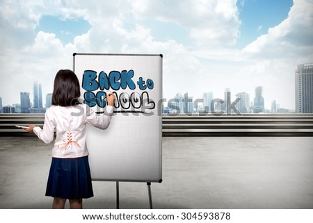 Little girl drawing on canvas back to school writing - stock photo
