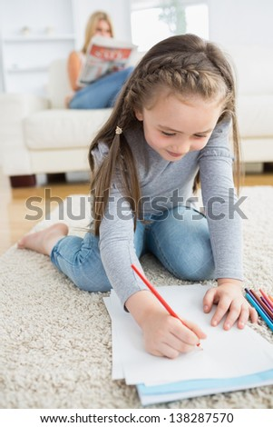 Little girl drawing on paper sitting on floor with mother reading newspaper on the couch - stock photo