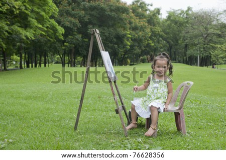 Little girl drawing /painting pictures in the park.