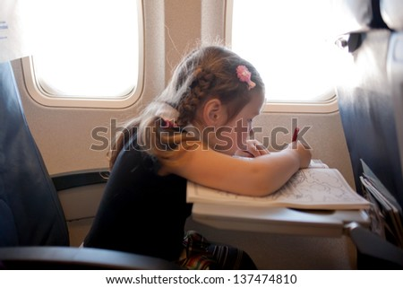 Little girl drawing while flying by plane - stock photo