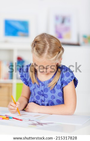 Little girl drawing with color pencil on table at home