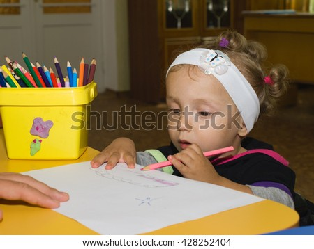 Little girl drawing with colored pencils on a white piece of paper - stock photo