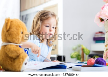 little girl drawing with crayons on the album. child having fun - stock photo