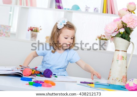 little girl drawing with crayons on the album. child having fun