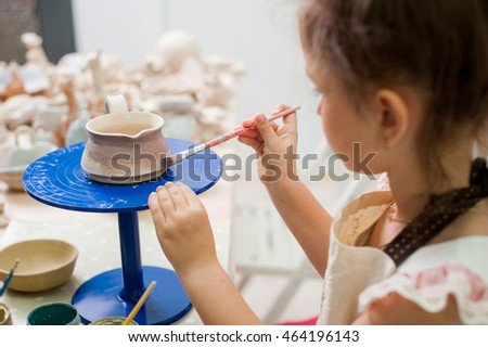 Little girl draws a brush on a cup made of clay
