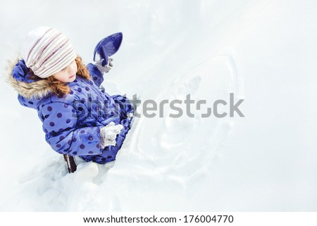 Little girl draws a smiley face on the snow - stock photo