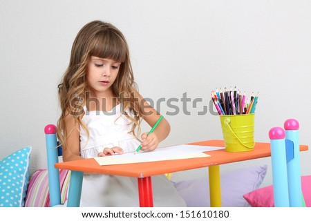 Little girl draws sitting at table in room on grey wall background - stock photo