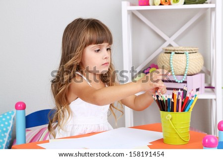 Little girl draws sitting at table in room on grey wall background