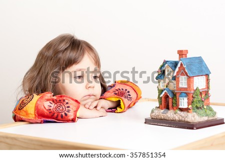 little girl dreaming about house - stock photo