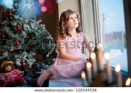 Little girl dreaming near Christmas tree - stock photo