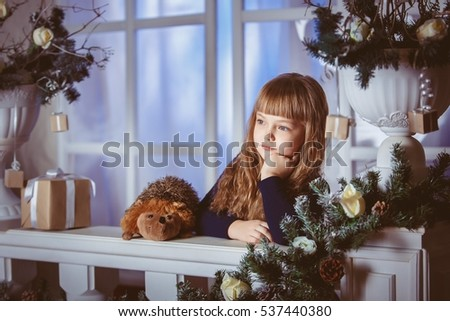 little girl dreams of a holiday on the Christmas window decoration