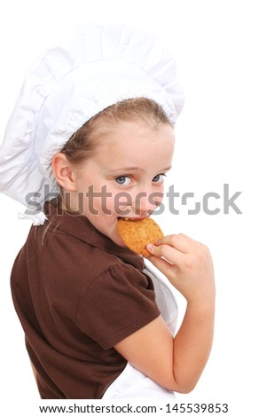 Little girl dressed as a chef eats a cookie