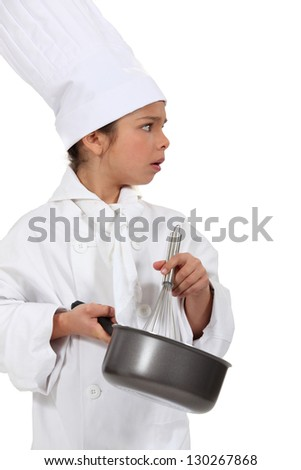little girl dressed as a chef holding a whisk - stock photo
