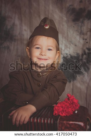 Little girl dressed as a Soviet soldier with carnations in their hands. Victory Day
