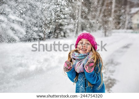 Little girl dressed in a blue coat and a pink hat grimacing in winter - stock photo
