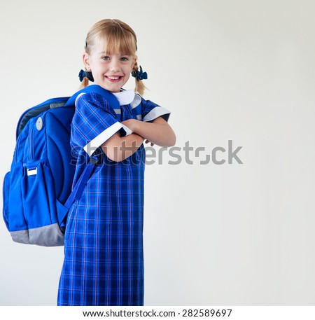 Little girl dressed in her school uniform and backpack ready to go to school