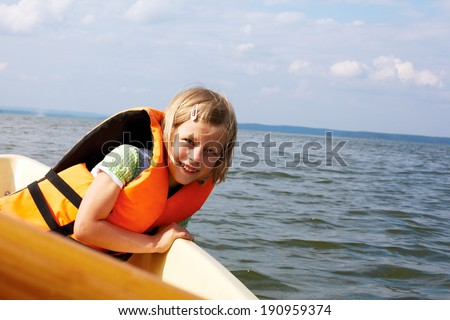 little girl dressed in life vest in a boat floats - stock photo